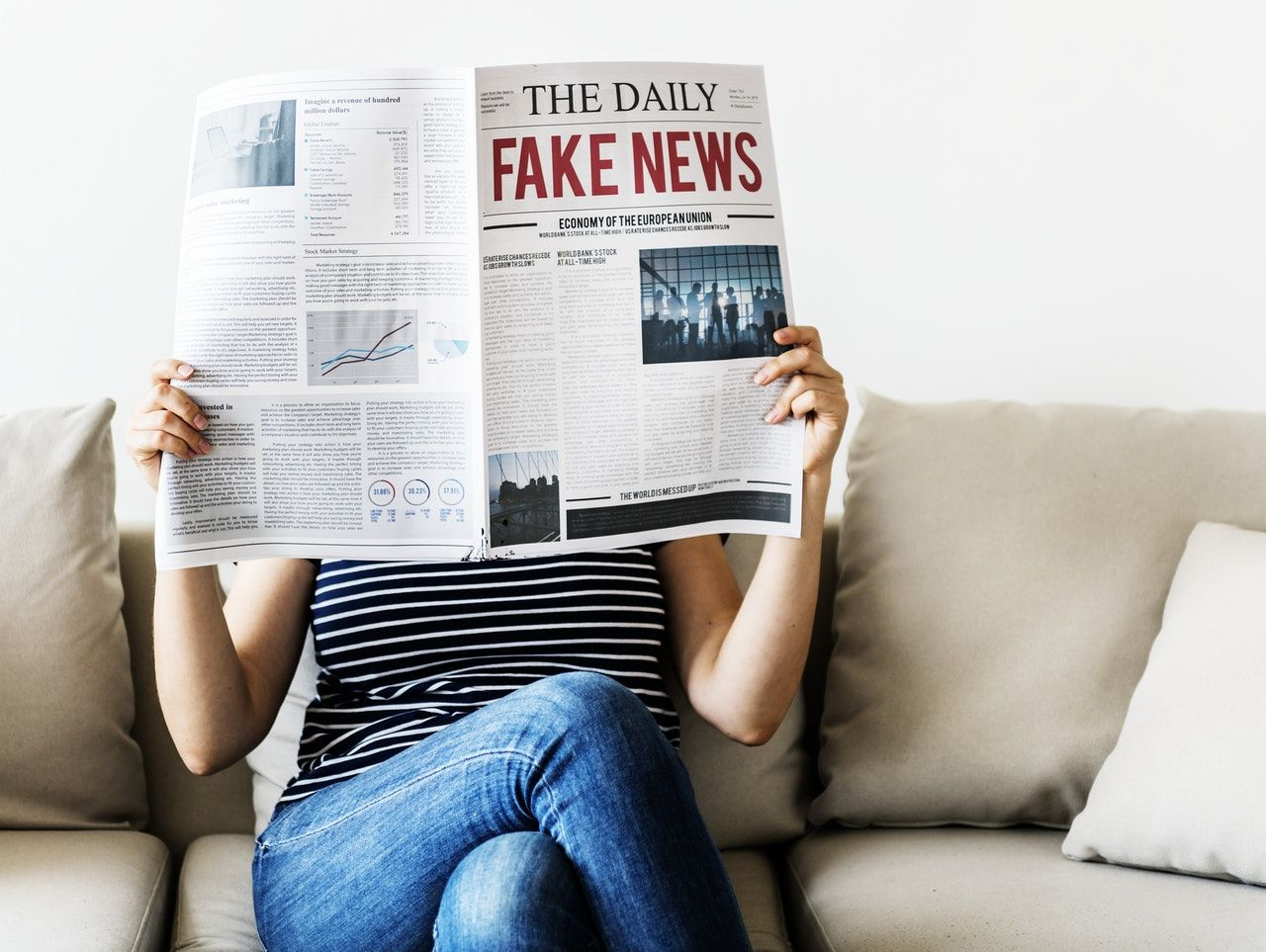 mulher segurando jornal com fake news