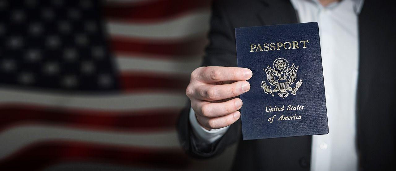 mão segurando passaporte americano com bandeira dos EUA ao fundo