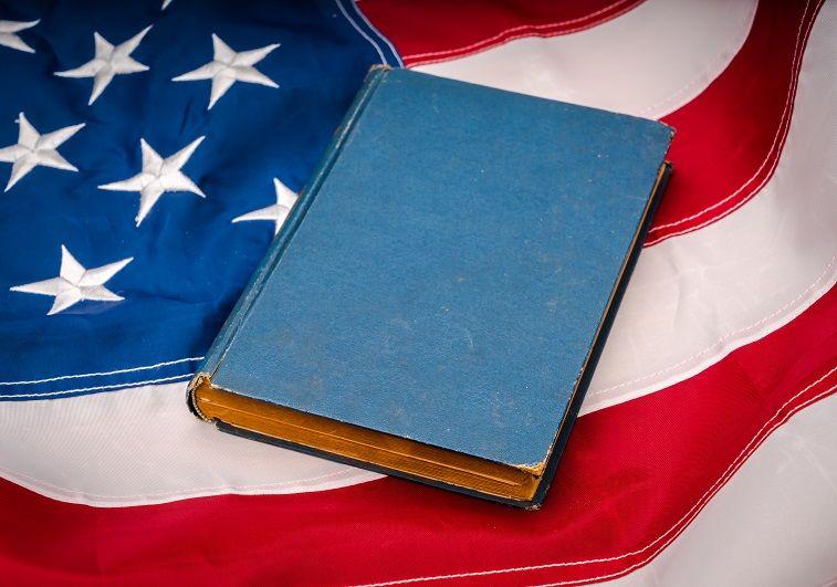 livro de capa azul sobre bandeira dos EUA