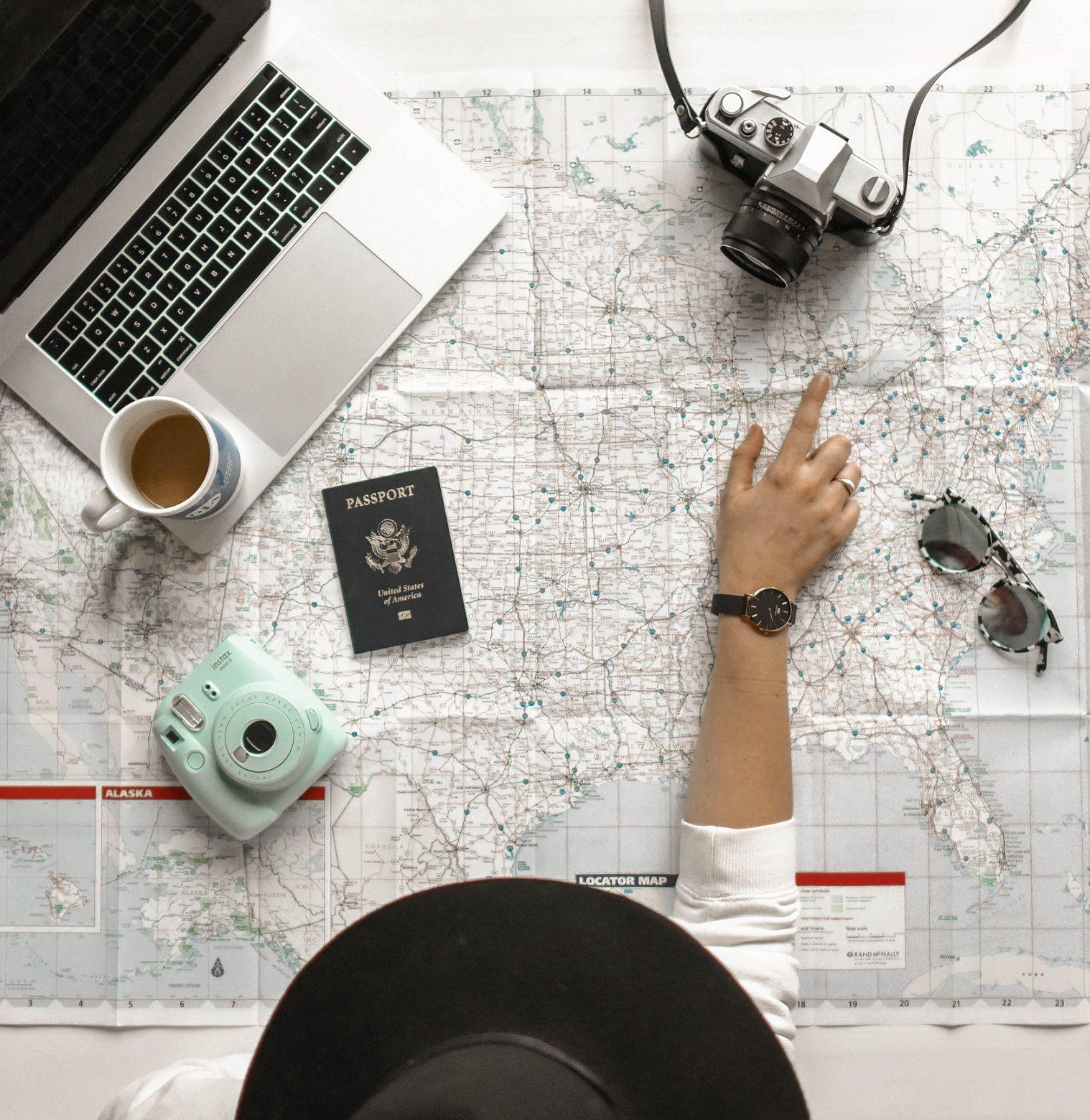 mulher com mapa, computador, câmera fotográfica e passaporte