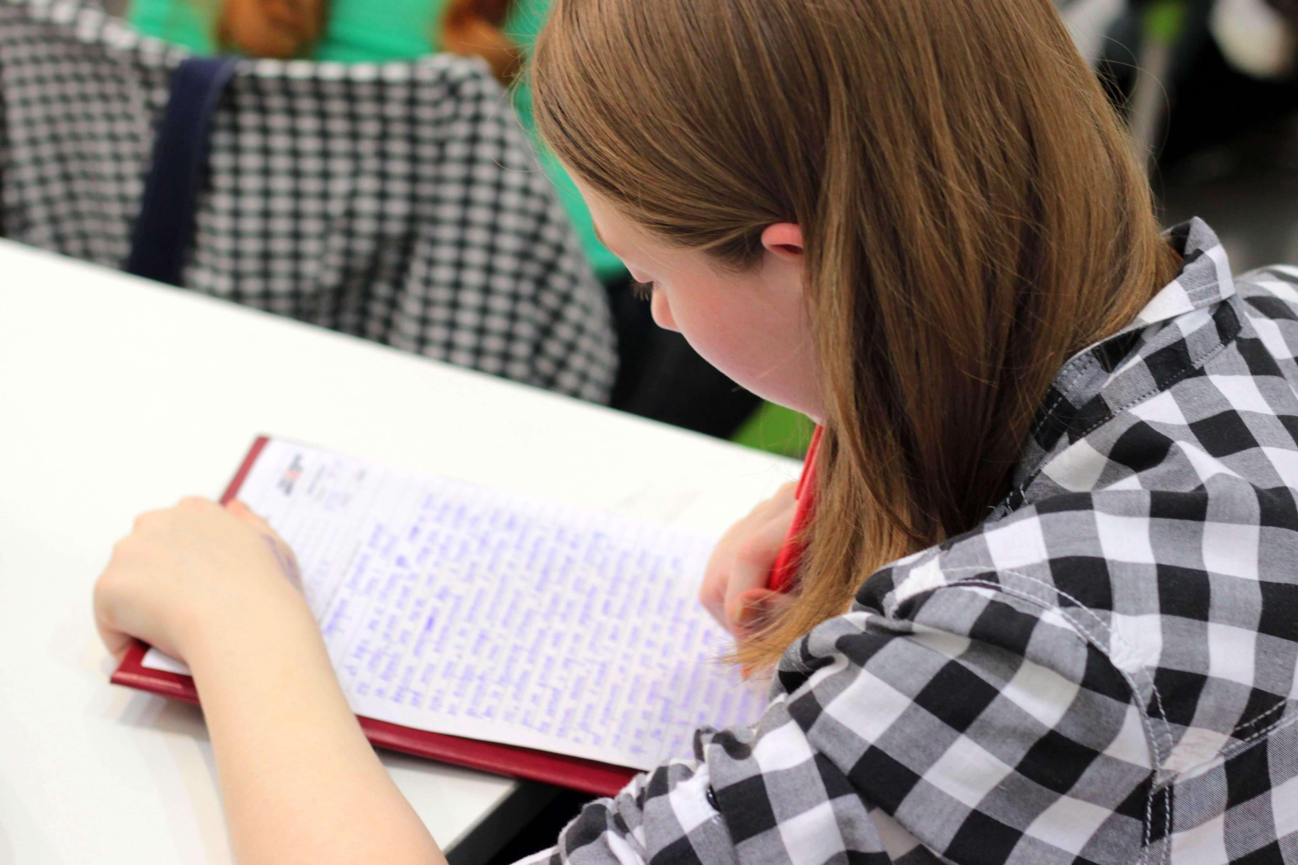 Estudante de cabeça baixa escrevendo em caderno