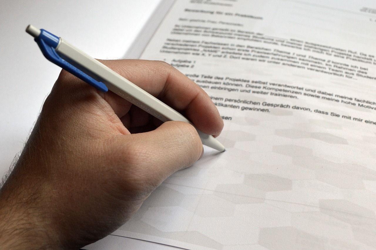 Mão com caneta assinando carta convite