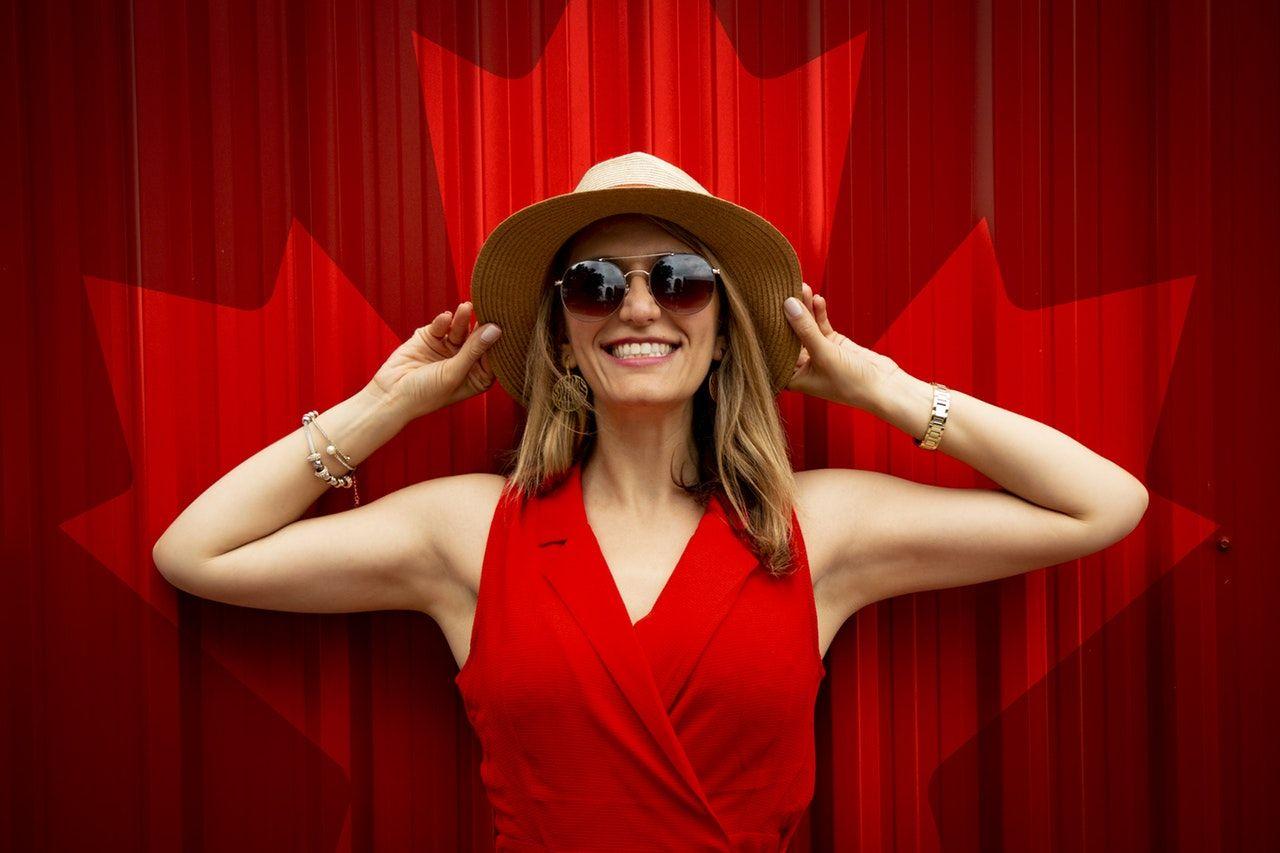 mulher sorrindo em frente à bandeira canadense