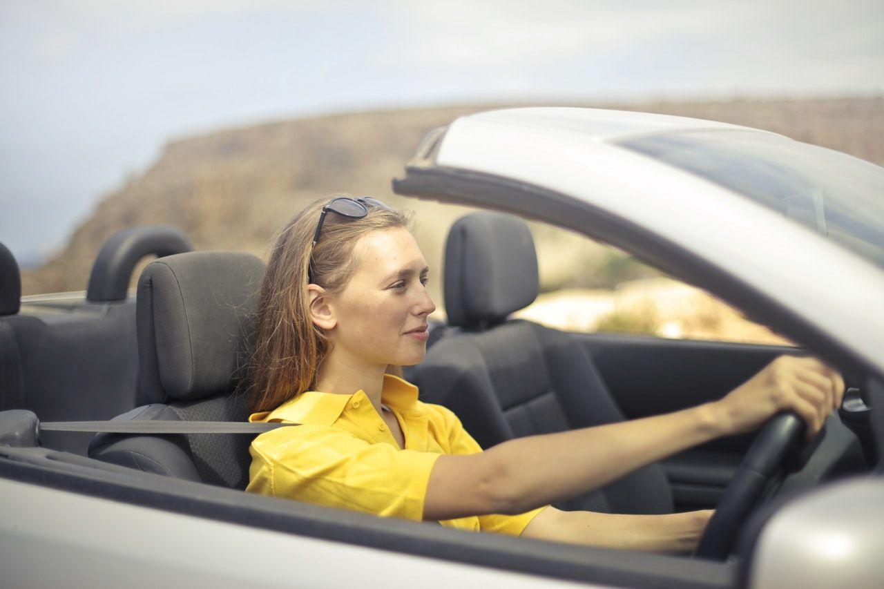 mulher dirigindo carro conversível