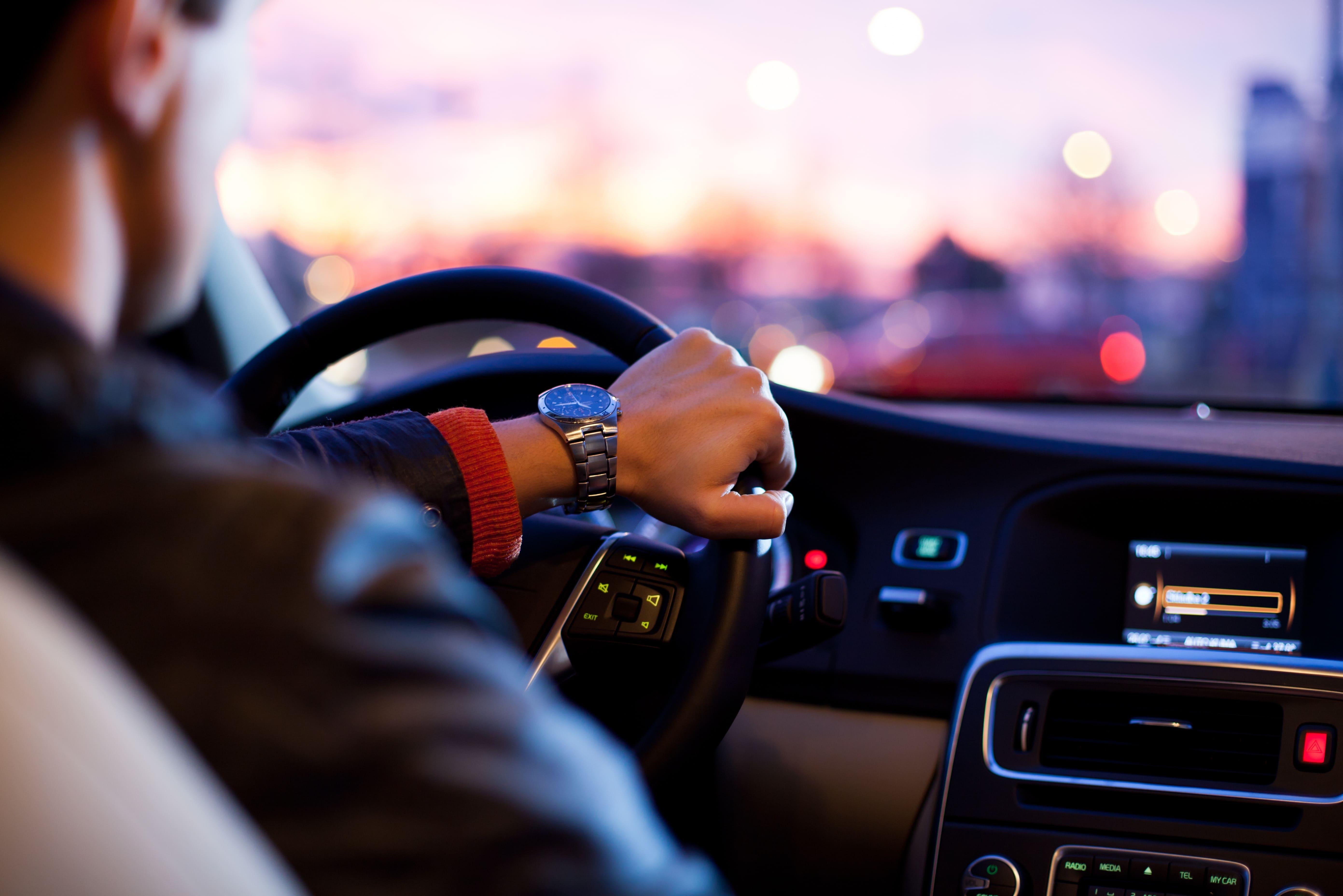 homem dirigindo com mãos no volante de um carro