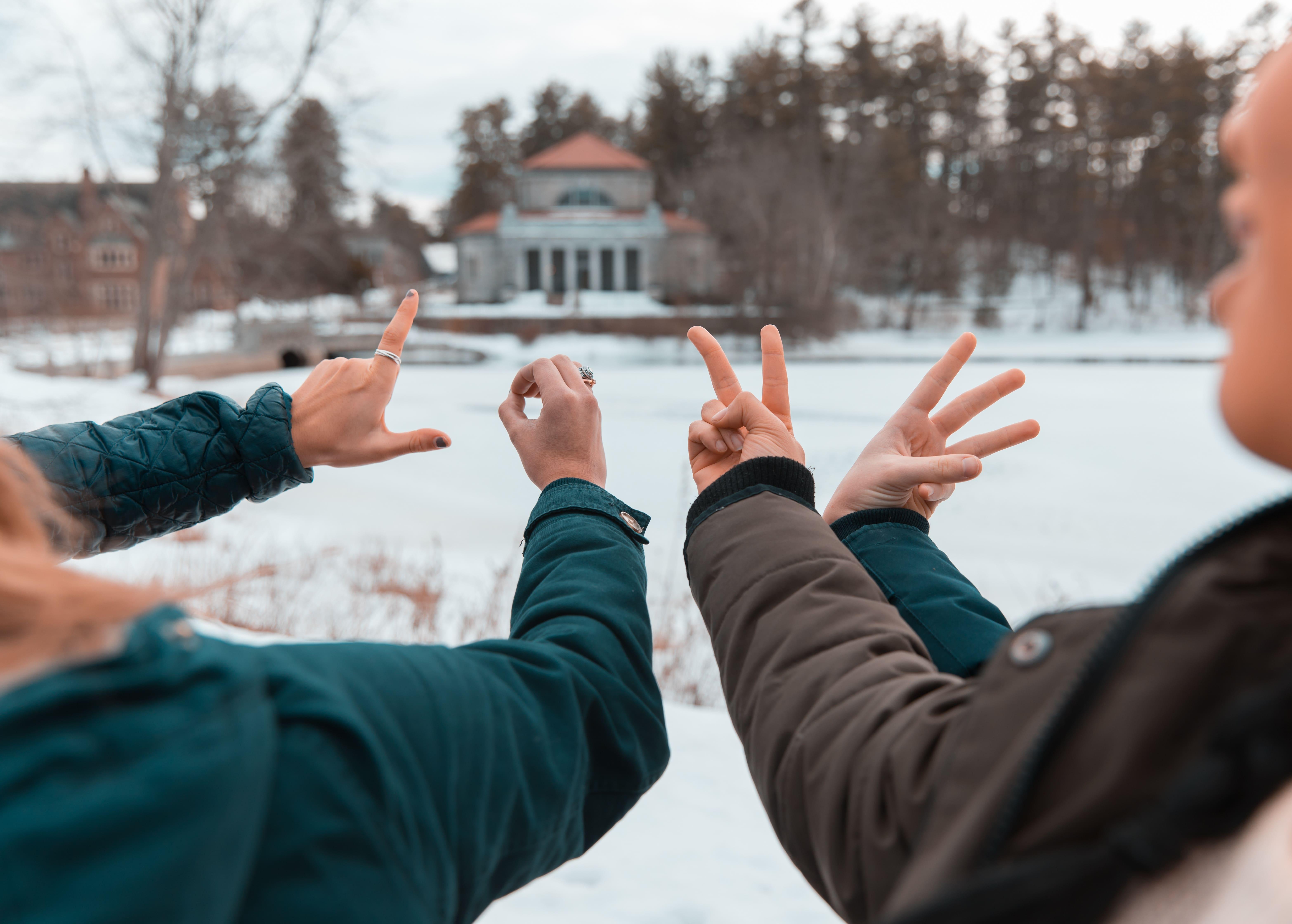mãos fazendo sinal de L O V Eno inverno
