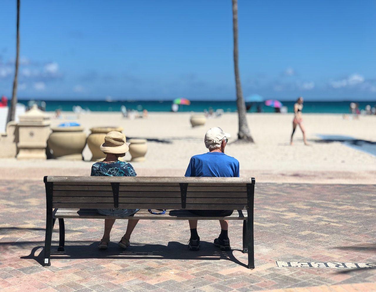 idosos sentados em banco à beira da praia na Flórida