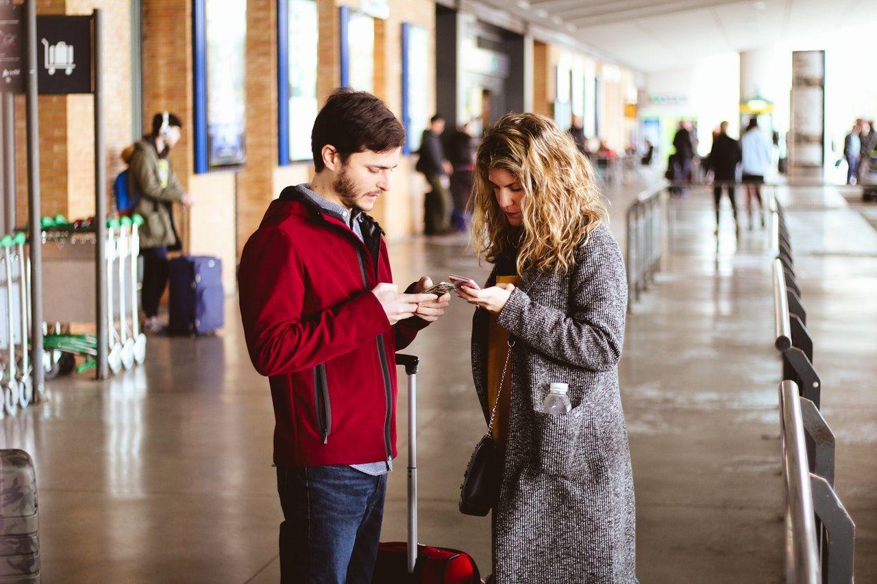 pessoas usando celular no aeroporto para acessar visto eletrônico