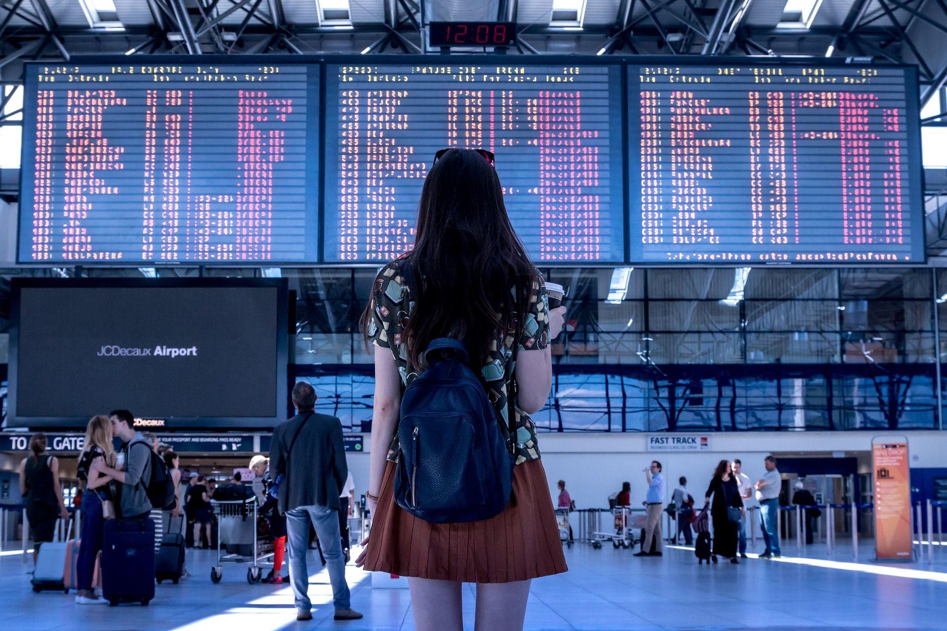 mulher olhando para painel em aeroporto