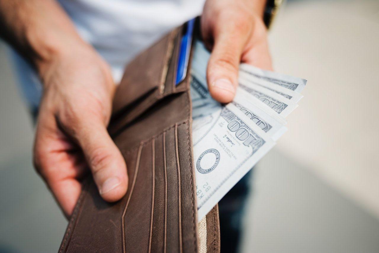 homem tirando notas da carteira