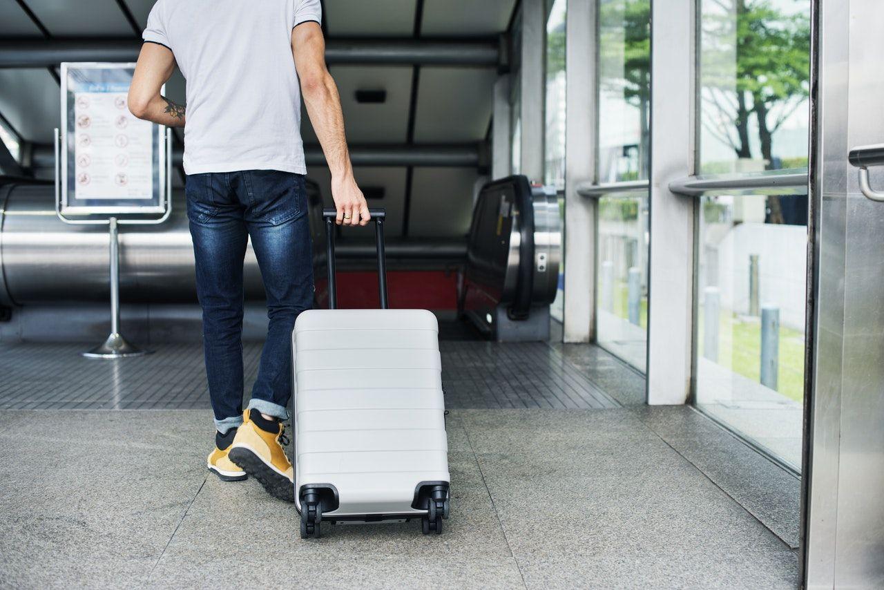 homem carregando mala em aeroporto