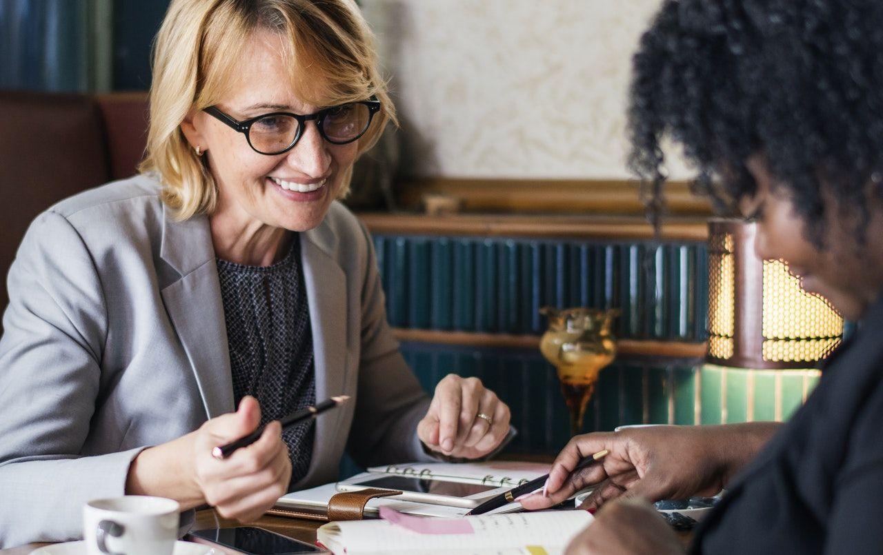 mulheres negociando em mesa com documentos