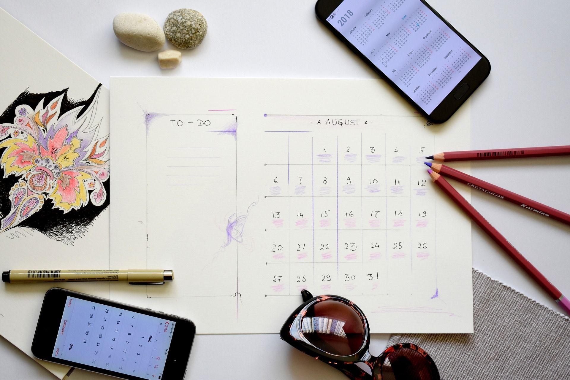 celular, calendário e lápis em cima de mesa