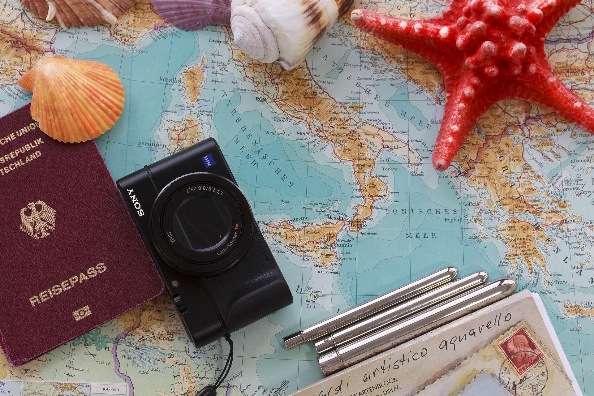 câmera fotográfica, documentos e objetos espalhados sobre mapa