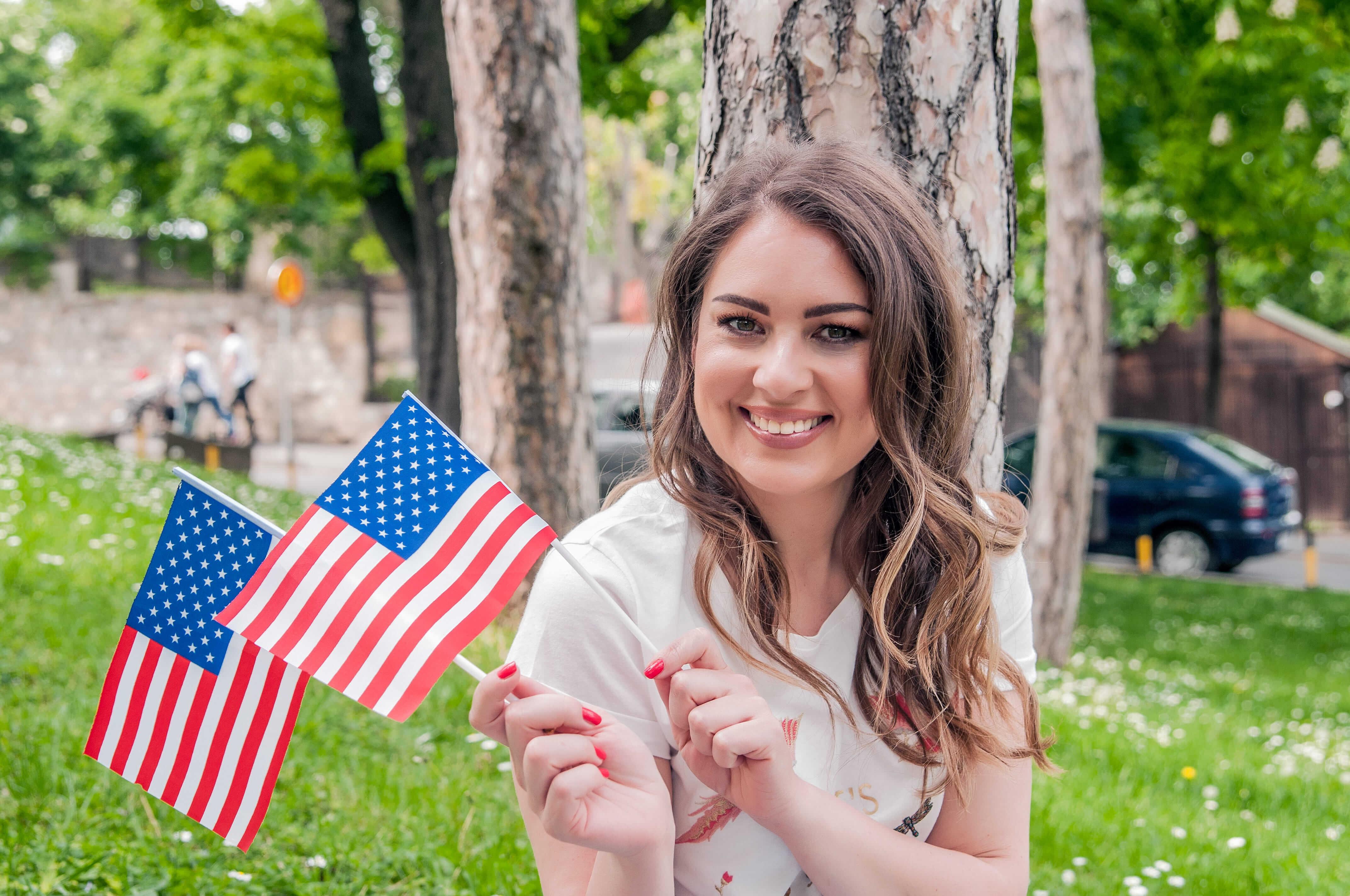 mulher segurando bandeirinhas dos estados unidos