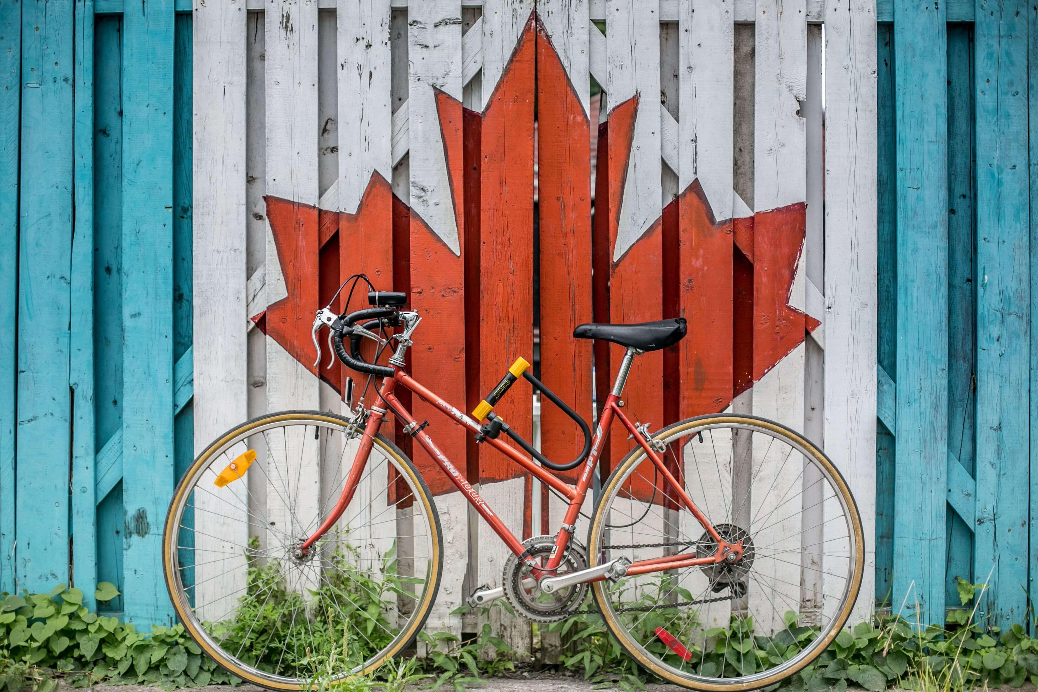 bicicleta em frente à pintura da bandeira canadense