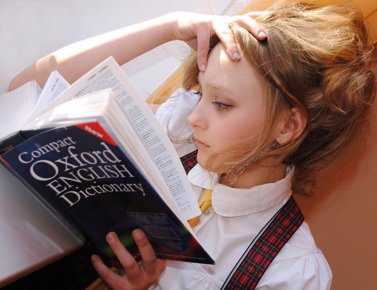 garota olhando dicionário de inglês