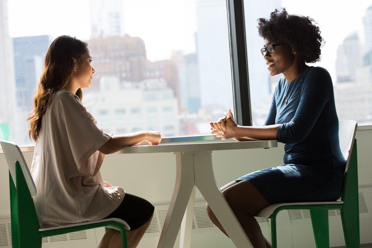 Duas mulheres conversando em uma mesa