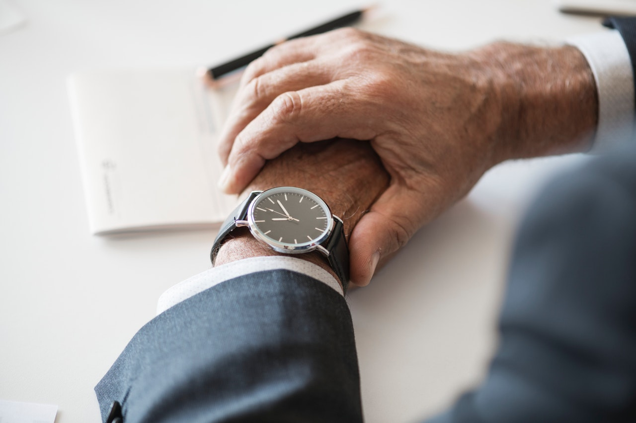 relógio de ponteiro em pulso de homem que precisa de visto americano de urgência