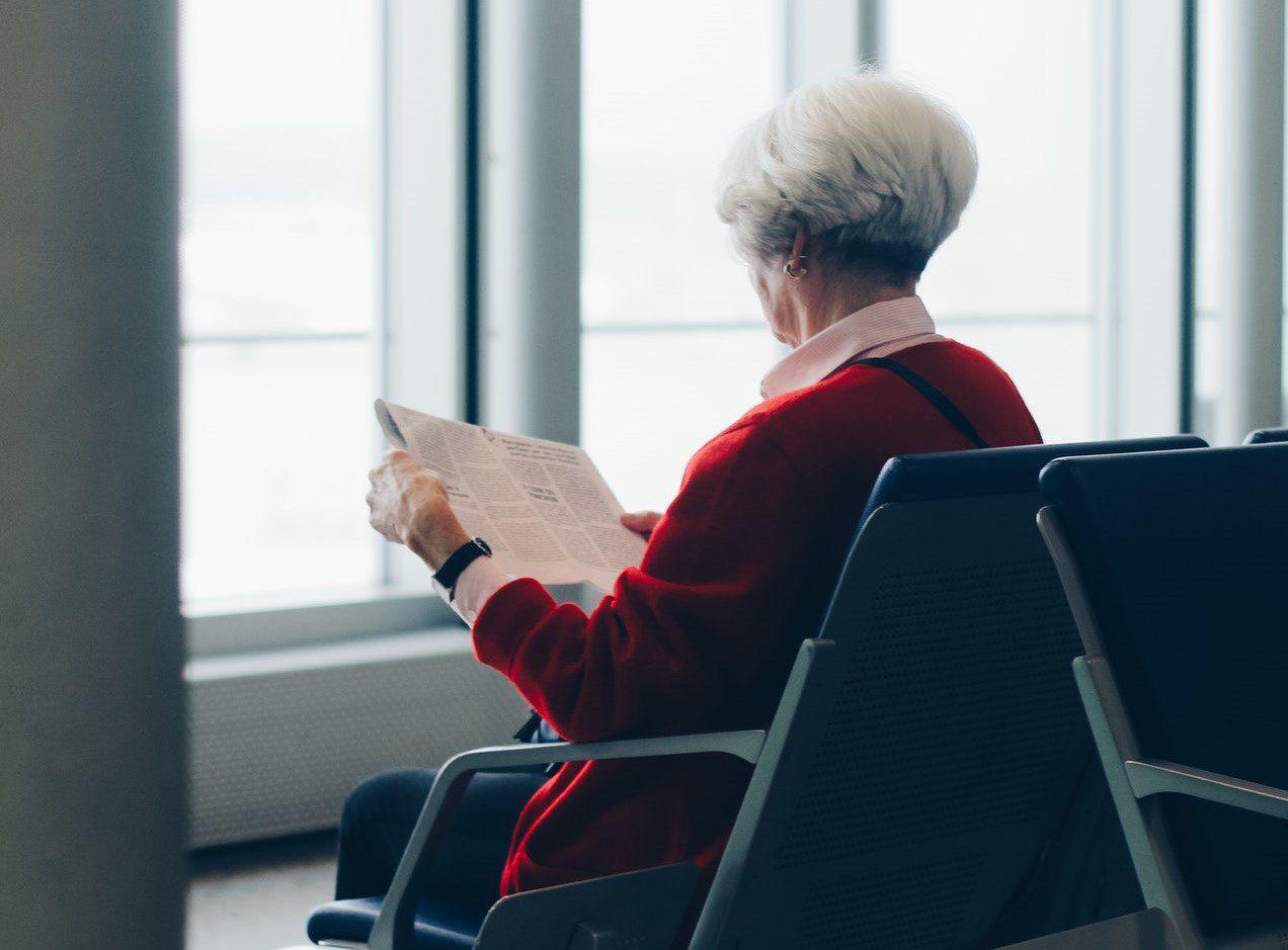 aposentada aguardando viagem internacional em aeroporto