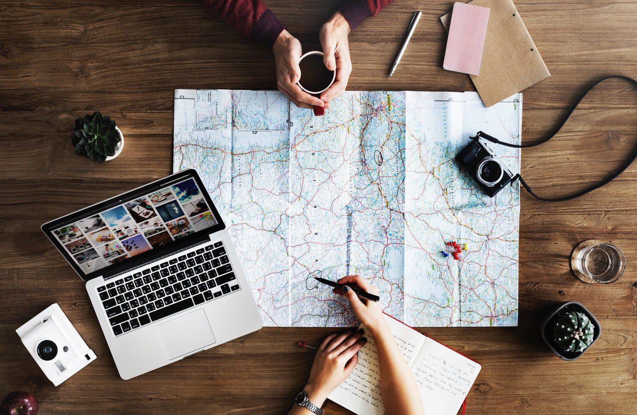 pessoas planjeando viagem em família com mapa, notebook e café