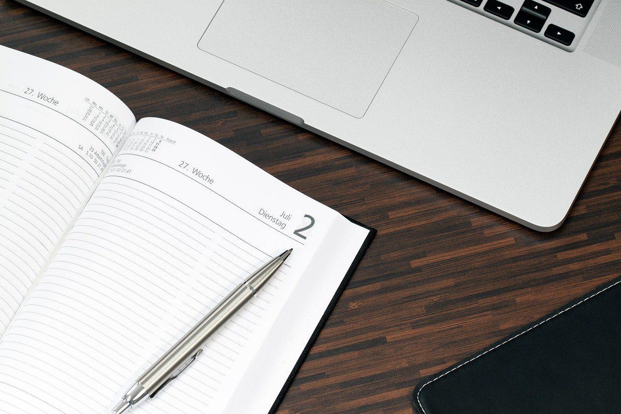 agenda e computador para planejamento de viagem