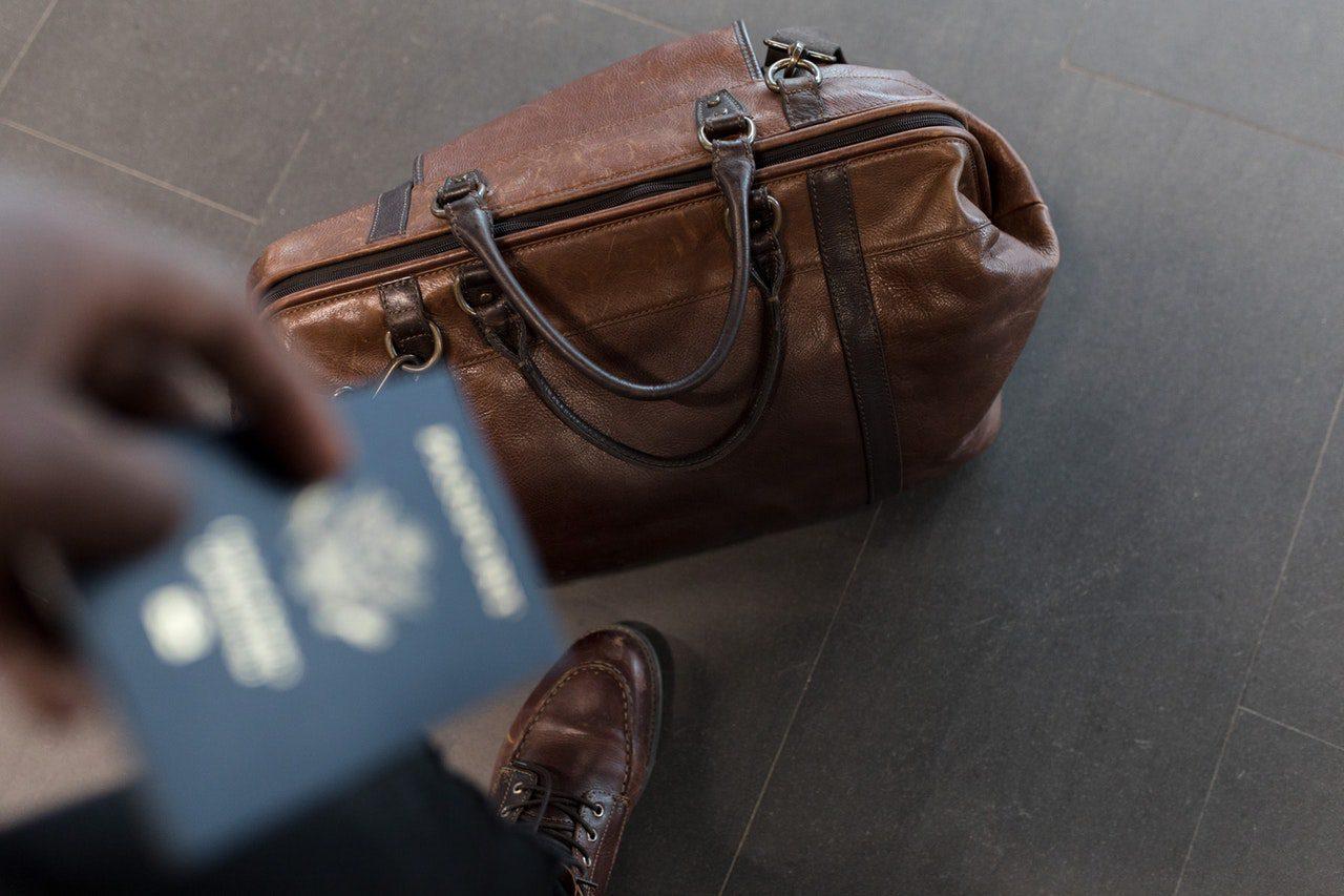 passaporte em mão e mala para viagem internacional