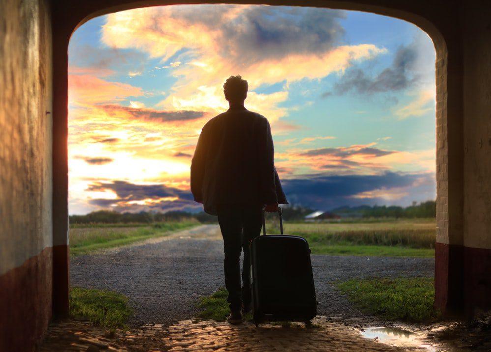 homem levando bagagem em estrada
