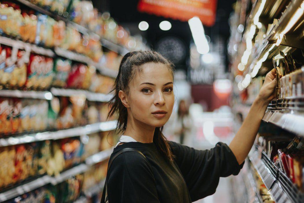 mulher escolhendo produtos em prateleira de supermercado